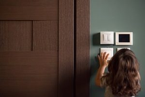 Girl facing a group of household temperature and lighting controls