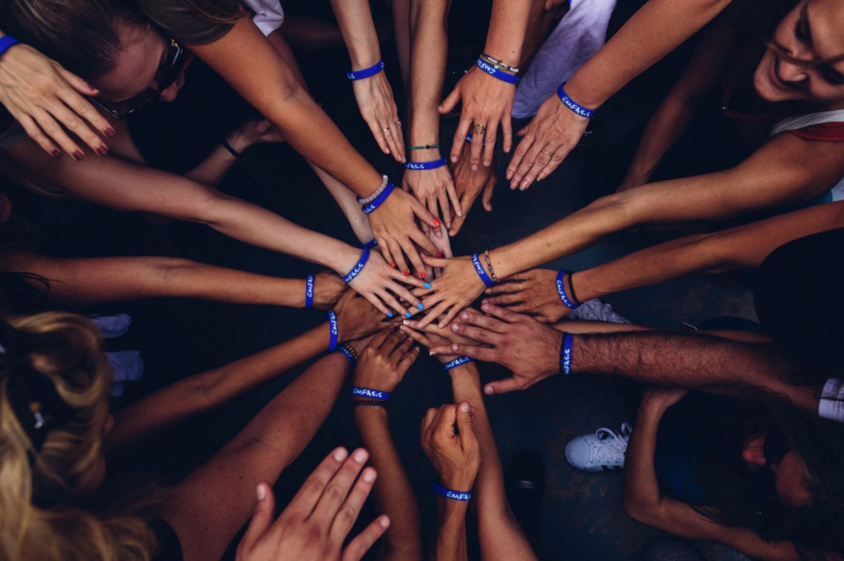 People in a circle bringing their hands together as a team