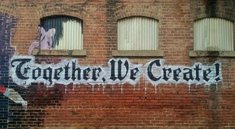 'Together we create' graffiti on wall