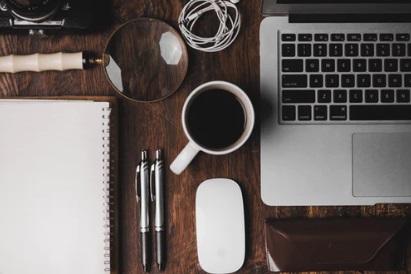 laptop, mug and stationery on a desk
