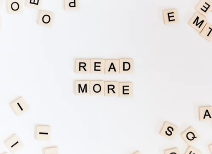 Scrabble tiles spelling out the words 'Read More'