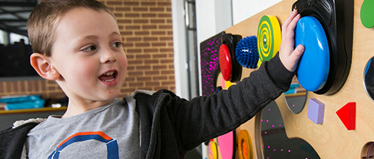 young boy playing with sensory wall