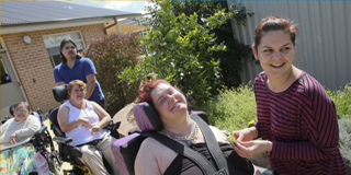 support workers assisting people with disability in wheelchairs