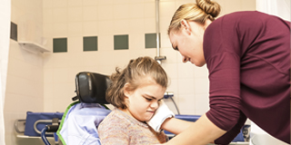 a child in a wheelchair; a female support worker gently touching her face while wearing a glove
