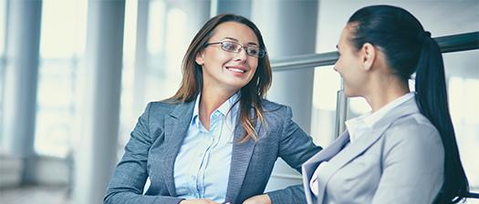 Two women sitting down in boardroom