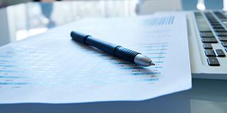 pen on a paper report; laptop beside it