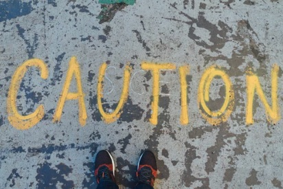 The word Caution written on the ground