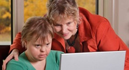 woman in red top assisting a person in green top read something on the laptop screen