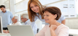 woman with long hair and older woman with short hair looking at a laptop screen