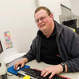 young man typing at a computer