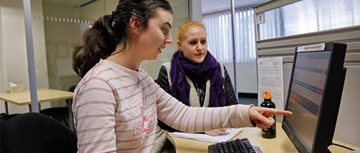 woman with intellectual disability pointing to a desktop computer screen; a woman sitting beside her looks at the monitor