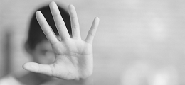 a boy holding up his palm to the camera, covering his face (blurry background)