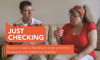 A man and a woman wearing glasses and holding a cup, chatting on the couch; The text 'Just Checking' and 'It's time to have a chat about cancer prevention for people with intellectual disability' superimposed on the image