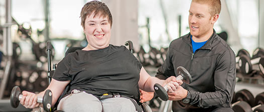 Woman in a wheelchair, lifting weights with both arms while being supported by a man