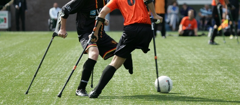 two athletes playing soccer while using crutches; they are both missing a leg