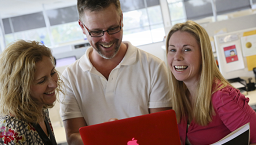 a woman and a man looking at a laptop; a woman smiling at the camera