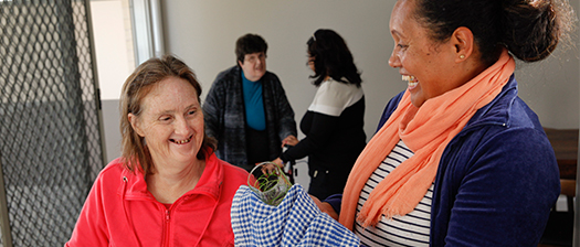woman in red (PWD) smiling at a woman wearing a striped white top, orange scarf and blue cardigan