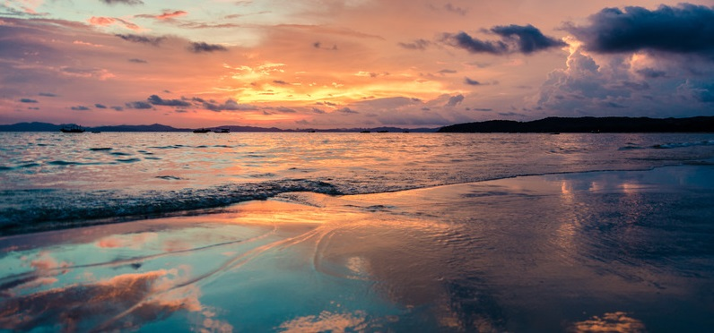 setting sun; clouds in the orange sky reflected in the blue water