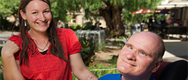 female support worker smiling; man in his wheelchair smiling at the camera