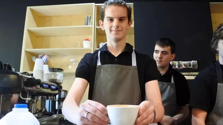 Image of young person in a cafe holding a coffee