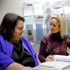 two women talking to each other. One woman pointing to a book on a desk.