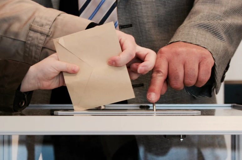 Person putting ballot into ballot box