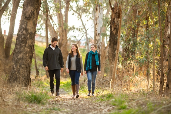 Three young people strolling down a path